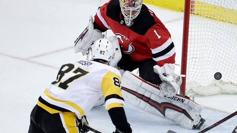 FILE - In this March 29, 2018, file photo, a shot by Pittsburgh Penguins center Sidney Crosby (87) enters the net behind New Jersey Devils goaltender Keith Kinkaid (1) for a goal during overtime of an NHL hockey game in Newark, N.J. Crosby makes it look easy. I think it's just instincts, Crosby said. (AP Photo/Julio Cortez, File)