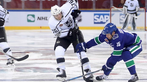 FILE - In this Sept. 23, 2017, file photo, Los Angeles Kings' Jonny Brodzinski, second from right, and the Vancouver Canucks' Derek Dorsett battle for control of the puck during the second period of their NHL China exhibition game at the Cadillac Arena in Beijing. The NHL is going back to China for two exhibition games this fall between the Boston Bruins and Calgary Flames. The league announced Wednesday, May 2, 2018, the Bruins and Flames will face off Sept. 15 in Shenzhen in southeast China and then again Sept. 19 in Beijing.(AP Photo/Mark Schiefelbein, File)