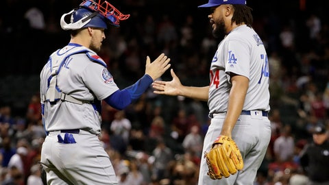 Los Angeles Dodgers relief pitcher Kenley Jansen, right, greets catcher Yasmani Grandal after a baseball game against the Arizona Diamondbacks on Wednesday, May 2, 2018, in Phoenix. The Dodgers won 2-1. (AP Photo/Matt York)