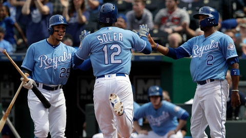 Kansas City Royals' Jorge Soler (12) is congratulated by Jon Jay (25) and Alcides Escobar (2) after scoring on a single by Lucas Duda during the sixth inning of a baseball game against the Detroit Tigers at Kauffman Stadium in Kansas City, Mo., Thursday, May 3, 2018. (AP Photo/Orlin Wagner)