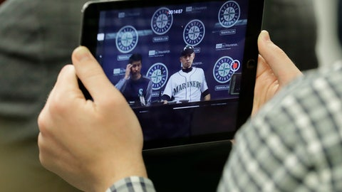 Seattle Mariners outfielder Ichiro Suzuki and Allen Turner, his translator, are shown on a tablet computer during a news conference, Thursday, May 3, 2018, in Seattle. Suzuki was released Thursday by the Mariners and is shifting into a front office role with the team, although he is not completely shutting the door on playing again. (AP Photo/Ted S. Warren)