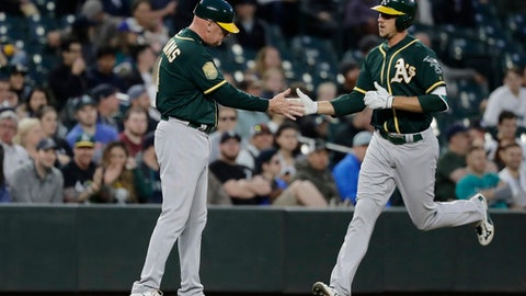 Oakland Athletics' Stephen Piscotty, right, greets third base coach Matt Williams after Piscotty hit a solo home run during the fifth inning of a baseball game against the Seattle Mariners, Thursday, May 3, 2018, in Seattle. (AP Photo/Ted S. Warren)
