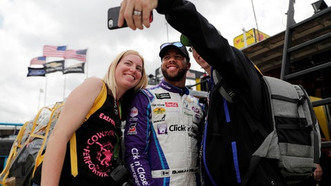 "FILE - In this April 6, 2018, file photo, Lydia Dickey, of Crowley, Texas, and her boyfriend, Chris Sharp, right, of Dallas, take a photo with Darrell Wallace Jr., center, after a practice session for a NASCAR Cup Series auto race in Fort Worth, Texas. Wallace was a budding photographer his first few years at the track, snapping away with his Canon 60D to show an insider's view of NASCAR. The hobby is on hold. Wallace fills his social media feeds with photos shot on his mobile phone. The fancy camera still has the lens cap on. ""I just don't have time for it now,"" Wallace said. ""This Cup schedule, it takes all your time away."" (AP Photo/Tony Gutierrez, File)"