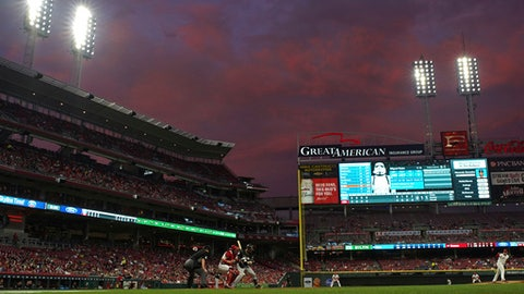 The sun sets as Miami Marlins' Miguel Rojas bats against Cincinnati Reds' starting pitcher Sal Romano in the fifth inning of a baseball game, Friday, May 4, 2018, in Cincinnati. (AP Photo/Aaron Doster)