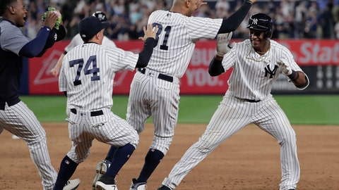 New York Yankees' Miguel Andujar, right, is mobbed by teammates after hitting a single to right field to drive in the winning run against the Cleveland Indians during the ninth inning of a baseball game Friday, May 4, 2018, in New York. The Yankees won 7-6. (AP Photo/Julie Jacobson)