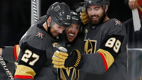 Vegas Golden Knights defenseman Shea Theodore (27), center Jonathan Marchessault, center, and right wing Alex Tuch (89) celebrate Tuch's goal against the San Jose Sharks during the second period of Game 5 of an NHL hockey second-round playoff series, Friday, May 4, 2018, in Las Vegas. (AP Photo/John Locher)