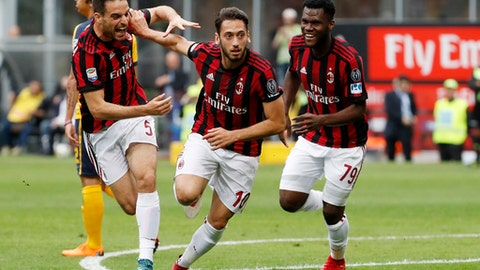 AC Milan's Hakan Calhanoglu, center, celebrates with his teammates Giacomo Bonaventura, left, Franck Kessie after scoring his side's opening goal during the Serie A soccer match between AC Milan and Hellas Verona at the San Siro stadium in Milan, Italy, Saturday, May 5, 2018. (AP Photo/Antonio Calanni)