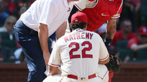 St. Louis Cardinals catcher Yadier Molina is checked on by assistant athletic trainer Chris Conroy and manager Mike Matheny after he was struck by a ball while catching during the ninth inning of the team's baseball game against the Chicago Cubs on Saturday, May 5, 2018, in St. Louis. Molina left the game. (Chris Lee/St. Louis Post-Dispatch via AP)