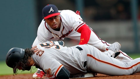 San Francisco Giants' Brandon Crawford (35) advances to second base on an error by Atlanta Braves right fielder Nick Makakis as second baseman Ozzie Albies (1) applies the late tag, after Crawford hit a single during the second inning of a baseball game Saturday, May 5, 2018, in Atlanta. (AP Photo/John Bazemore)