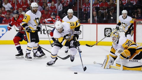 Pittsburgh Penguins right wing Bryan Rust (17) skates away with the puck in front of Penguins goaltender Matt Murray (30) during the second period of Game 5 in the second round of the NHL Stanley Cup hockey playoffs against the Washington Capitals, Saturday, May 5, 2018, in Washington. (AP Photo/Alex Brandon)