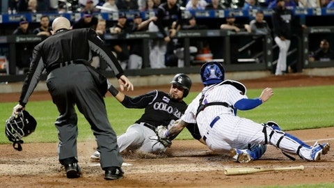 ADDS IN THE NINTH INNING - Colorado Rockies' Noel Cuevas, center, is tagged out by New York Mets catcher Tomas Nido, right, as home plate umpire Mike Estabrook watches in the ninth inning of a baseball game Saturday, May 5, 2018, in New York. (AP Photo/Frank Franklin II)
