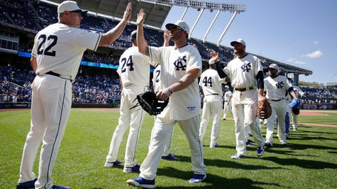 Kansas City Royals pitching coach Cal Eldred (22) congratulates Mike Moustakas, center, and other teammates as they walk off the field following their win over the Detroit Tigers at Kauffman Stadium in Kansas City, Mo., Sunday, May 6, 2018. Royals' Lucas Duda, second from right, and Kelvin Herrera, right, also receive congratulations. (AP Photo/Colin E. Braley)