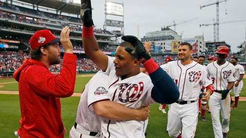 Washington Nationals' Wilmer Difo, center, celebrates his walkoff RBI-single with Daniel Murphy, left, and others after a baseball game against the Philadelphia Phillies at Nationals Park, Sunday, May 6, 2018, in Washington. (AP Photo/Alex Brandon)