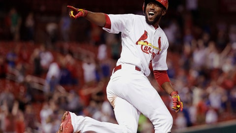 St. Louis Cardinals' Dexter Fowler, right, looks back into the dugout and celebrates his walk-off two-run home run off Chicago Cubs relief pitcher Luke Farrell during the 14th inning of a baseball game Monday, May 7, 2018, in St. Louis. The Cardinals won 4-3. (AP Photo/Charles Rex Arbogast)