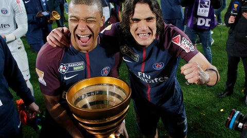 """FILE - In this Saturday, March 31, 2018 file picture PSG's Edinson Cavani celebrates with Kylian Mbappe holding the trophy after winning the League Cup final soccer match against Monaco in Bordeaux, southwestern France. In the buildup to Tuesday's final at the Stade de France against Paris Saint-Germain, the third-division minnows have been invited to stay at Clairefontaine, the national football center known as """"The Castle"""" where France's international players prepare for their matches. (AP Photo/Thibault Camus, File)"""