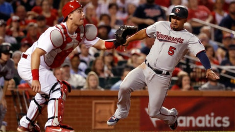 Minnesota Twins' Eduardo Escobar (5) scores as St. Louis Cardinals catcher Carson Kelly waits for the throw during the sixth inning of a baseball game Monday, May 7, 2018, in St. Louis. (AP Photo/Jeff Roberson)