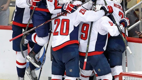 Washington Capitals left wing Jakub Vrana (13) leaps onto the pile celebrating Capitals' Evgeny Kuznetsovs' game-winning goal during the overtime period in Game 6 of an NHL second-round hockey playoff series against the Pittsburgh Penguins in Pittsburgh, Monday, May 7, 2018. The Capitals won the game, 2-1 to win the series, four games to two. (AP Photo/Gene J. Puskar)