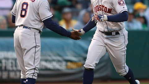 Houston Astros' George Springer, right, is congratulated by third base coach Gary Pettis (8) after hitting a three run home run off Oakland Athletics' Brett Anderson during the second inning of a baseball game Monday, May 7, 2018, in Oakland, Calif. (AP Photo/Ben Margot)