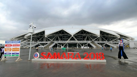 In this photo taken on Saturday, April 28, 2018, an artist, right, performs waiting for football fans at the new the World Cup stadium in Samara prior to the Russian league soccer match between Krylia Sovetov (Wings of Soviets) and Fakel (Torch) , Russia. (AP Photo/Yuri Strelets)