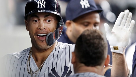 New York Yankees designated hitter Giancarlo Stanton celebrates with teammates in the dugout after hitting a solo home run during the fourth inning of a baseball game against the Boston Red Sox in New York, Tuesday, May 8, 2018. (AP Photo/Kathy Willens)
