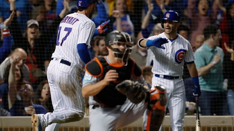 Chicago Cubs' Kris Bryant, left, celebrates with teammate Tommy La Stella, right, after scoring, near Miami Marlins catcher J.T. Realmuto during the eighth inning of a baseball game Tuesday, May 8, 2018, in Chicago. (AP Photo/Jim Young)