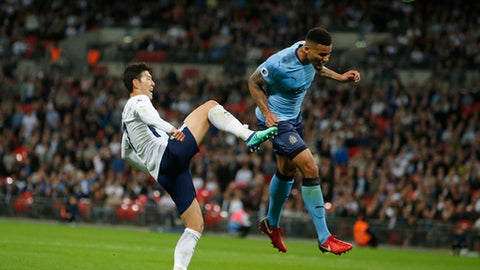 Newcastle United's Jamaal Lascelles clears the ball before Tottenham Hotspur's Son Heung-min, left, during the English Premier League soccer match between Tottenham Hotspur and Newcastle United at Wembley Stadium, in London, England, Wednesday, May 9, 2018. (AP Photo/Alastair Grant)