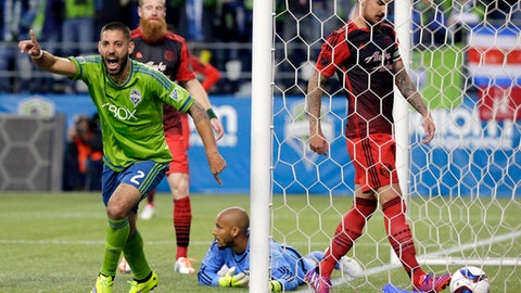 FILE - In this April 26, 2015, file photo, Seattle Sounders' Clint Dempsey, left, celebrates after he scored a goal against Portland Timbers goalkeeper Adam Kwarasey, second from right, as Timbers' Alvas Powell, right, stands in the goal during the second half of an MLS soccer match in Seattle. The Timbers host the Sounders on Sunday in the 100th meeting between the two rivals from the Pacific Northwest. (AP Photo/Ted S. Warren, File)