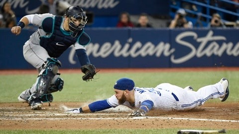 Toronto Blue Jays' Russell Martin, right, slides safely into home plate as Seattle Mariners catcher Mike Zunino watches during the eighth inning of a baseball game Wednesday, May 9, 2018, in Toronto. (Nathan Denette/The Canadian Press via AP)