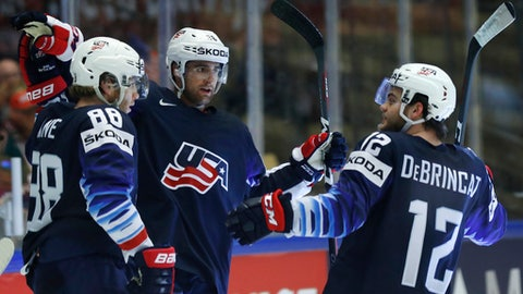 Colin White, center, of the United States celebrates with teammates Patrick Kane, left, and Alex Debrincat, right, after scoring his teams second goal during the Ice Hockey World Championships group B match between United States and Latvia at the Jyske Bank Boxen arena in Herning, Denmark, Thursday, May 10, 2018. (AP Photo/Petr David Josek)