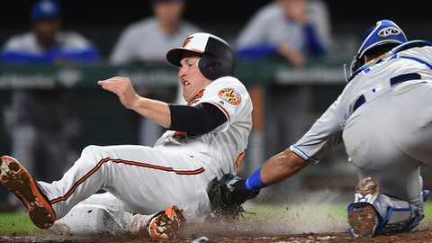 Baltimore Orioles' Mark Trumbo, left, crosses the plate and scores on a single by Anthony Santander as Kansas City Royals catcher Salvador Perez apples the tag during the fifth inning of baseball game Thursday, May 10, 2018, in Baltimore. (AP Photo/Gail Burton)