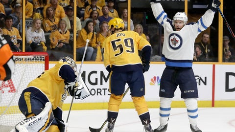 Winnipeg Jets center Paul Stastny, right, celebrates after teammate Tyler Myers, not shown, scored a goal against Nashville Predators goalie Pekka Rinne, left, of Finland, during the first period in Game 7 of an NHL hockey second-round playoff series Thursday, May 10, 2018, in Nashville, Tenn. Also defending for the Predators is Roman Josi (59), of Switzerland. (AP Photo/Mark Humphrey)
