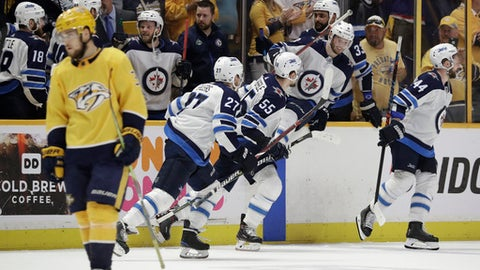 Winnipeg Jets players jump onto the ice to celebrate as Nashville Predators left wing Viktor Arvidsson, left, of Sweden, skates to his bench after the Jets' 5-1 win in Game 7 of an NHL hockey second-round playoff series Thursday, May 10, 2018, in Nashville, Tenn. The Jets advanced to the Western Conference final. (AP Photo/Mark Humphrey)