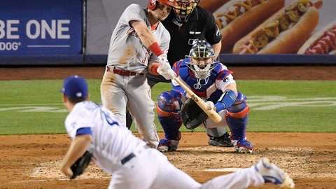 Cincinnati Reds' Scooter Gennett hits a solo home run off Los Angeles Dodgers relief pitcher Daniel Hudson, foreground, during the eighth inning of a baseball game Thursday, May 10, 2018, in Los Angeles. (AP Photo/Mark J. Terrill)