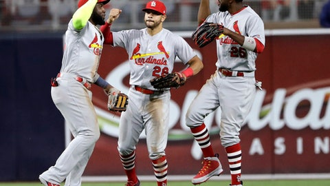 St. Louis Cardinals left fielder Marcell Ozuna, right, celebrates with center fielder Tommy Pham, center, and right fielder Tommy Pham after the Cardinals defeated the San Diego Padres 2-1 in a baseball game Thursday, May 10, 2018, in San Diego. (AP Photo/Gregory Bull)