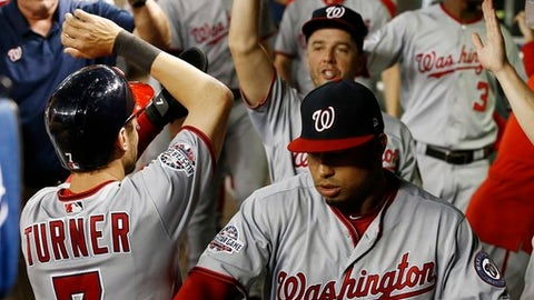 Washington Nationals' Trea Turner (7) celebrates, after scoring against the Arizona Diamondbacks, with Moises Sierra, front right, and Brandon Kintzler, back right, during the 11th inning of a baseball game Thursday, May 10, 2018, in Phoenix. (AP Photo/Ross D. Franklin)
