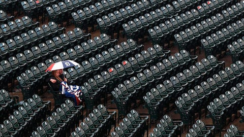 Detroit Tigers fans sit in the stands under an umbrella in the rain before the team's baseball game against the Seattle Mariners in Detroit, Friday, May 11, 2018. (AP Photo/Paul Sancya)