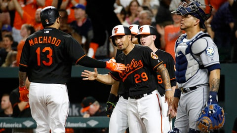 Baltimore Orioles' Jace Peterson (29) greets teammate Manny Machado in front of Tampa Bay Rays catcher Wilson Ramos, front right, after scoring on Machado's grand slam in the seventh inning of a baseball game, Friday, May 11, 2018, in Baltimore. (AP Photo/Patrick Semansky)