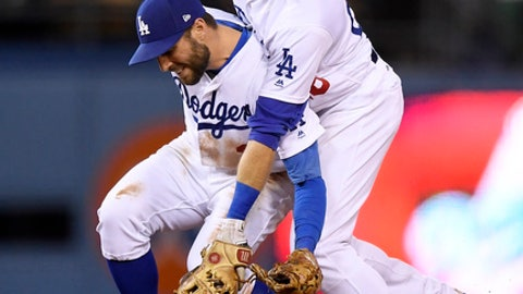 Los Angeles Dodgers shortstop Chris Taylor, left, and second baseman Chase Utley collide as they try to field a ball hit by Cincinnati Reds' Jose Peraza during the sixth inning of a baseball game Friday, May 11, 2018, in Los Angeles. Utley ended up with the ball and forced out Jesse Winker at second. (AP Photo/Mark J. Terrill)