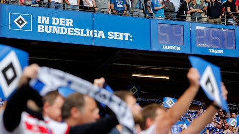 Supporters sing underneath a clock, indicating Hamburg's uninterrupted time of Bundesliga membership, prior to the German Bundesliga soccer match between Hamburger SV and VfL Borussia Moenchengladbach in Hamburg, Germany, Saturday, May 12, 2018. (AP Photo/Michael Sohn)