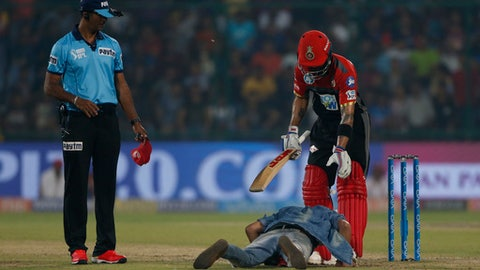 A  fan of  Royal Challengers Bangalore captain Virat Kohli reacts in front of him after he came onto the field during the VIVO IPL cricket T20 match against Delhi Daredevils' in New Delhi, India, Saturday, May 12, 2018. (AP Photo/Altaf Qadri)