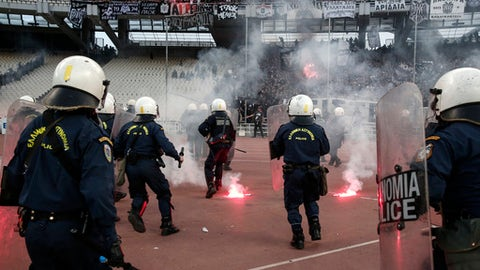 Greek policemen try to avoid flares thrown at them by fans ahead of a Greek Cup final in Athens' Olympic stadium in Athens, Saturday, May 12, 2018. (AP Photo/Yorgos Karahalis)