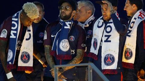 PSG's Dani Alves, center, and Neymar, second right, talk during the League One winner's trophy ceremony after the soccer match between Paris Saint-Germain and Stade Rennais at the Parc des Princes stadium in Paris, Saturday May 12, 2018. (AP Photo/Christophe Ena)