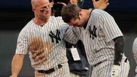 New York Yankees' Brett Gardner, left, congratulates Neil Walker after Walker drove in the winning run against the Oakland Athletics during the eleventh inning of a baseball game, Saturday, May 12, 2018, in New York. The Yankees won 7-6. (AP Photo/Julie Jacobson)