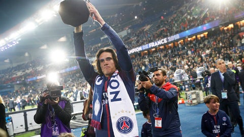 PSG's Edinson Cavani holds the French League One trophy after the soccer match between Paris Saint-Germain and Stade Rennais at the Parc des Princes stadium in Paris, Saturday May 12, 2018. (AP Photo/Christophe Ena)
