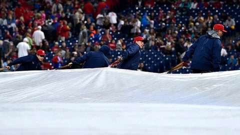 Grounds crews roll the tarp onto the field prior to a baseball game between the Philadelphia Phillies and the New York Mets as heavy storms were anticipated, Saturday, May 12, 2018, in Philadelphia. The game was postponed due to rain. (AP Photo/Derik Hamilton)