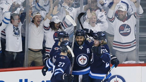 Winnipeg Jets' Nikolaj Ehlers (27), Mark Scheifele (55), Dustin Byfuglien (33) and Patrik Laine (29) celebrate Byfuglien's goal against the Vegas Golden Knights during the first period of Game 1 of the NHL hockey playoffs Western Conference final, Saturday, May 12, 2108, in Winnipeg, Manitoba. (John Woods/The Canadian Press via AP)