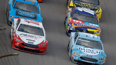 Kevin Harvick (4) leads the pack during the NASCAR Cup Series auto race at Kansas Speedway on Saturday, May 12, 2018, in Kansas City, Kan. (AP Photo/Charlie Riedel)