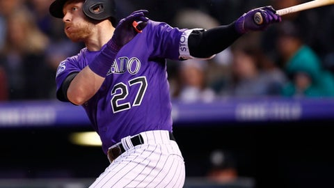 Colorado Rockies' Trevor Story follows the flight of his RBI-double off Milwaukee Brewers starting pitcher Brent Suter in the third inning of a baseball game Saturday, May 12, 2018, in Denver. (AP Photo/David Zalubowski)