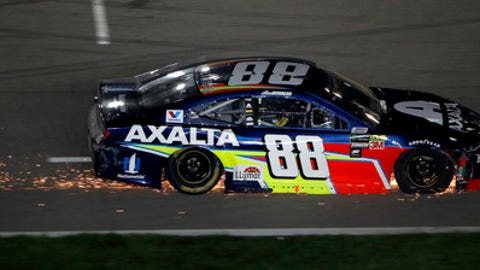 Sparks trail from Alex Bowman's car as he heads for the pits during the NASCAR Cup Series auto race at Kansas Speedway on Saturday, May 12, 2018, in Kansas City, Kan. (AP Photo/Charlie Riedel)