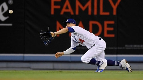 Los Angeles Dodgers center fielder Enrique Hernandez makes a catch on a ball hit by Cincinnati Reds' Scott Schebler during the seventh inning of a baseball game Saturday, May 12, 2018, in Los Angeles. (AP Photo/Mark J. Terrill)
